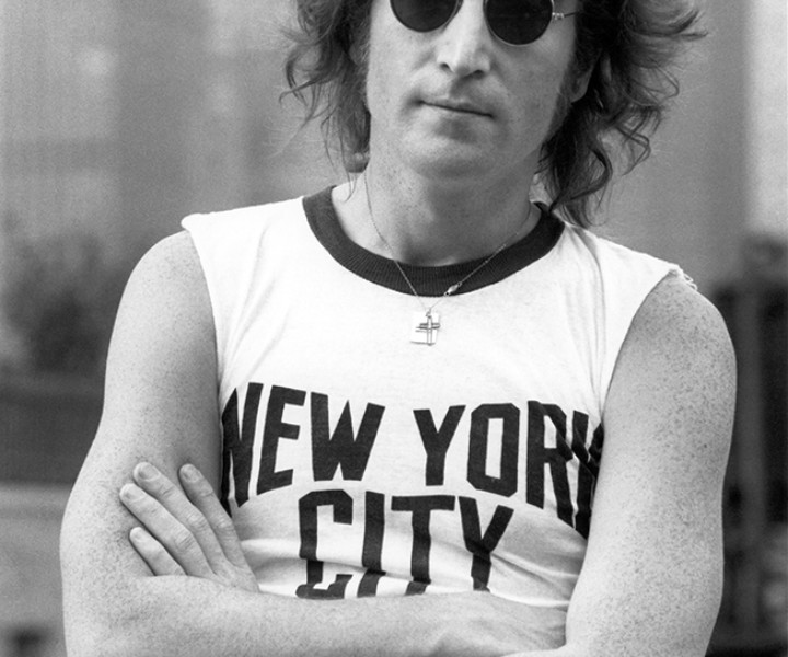 After taking portrait photos of John Lennon's face on the roof of Lennon's New York apartment, I decided to take more photos for publicity.  I had given John a NYC T-shirt a year earlier and with the skyline all around I asked John if he still had it as this would be the perfect place to wear it.  John went and put it on to make this now iconic photo.
