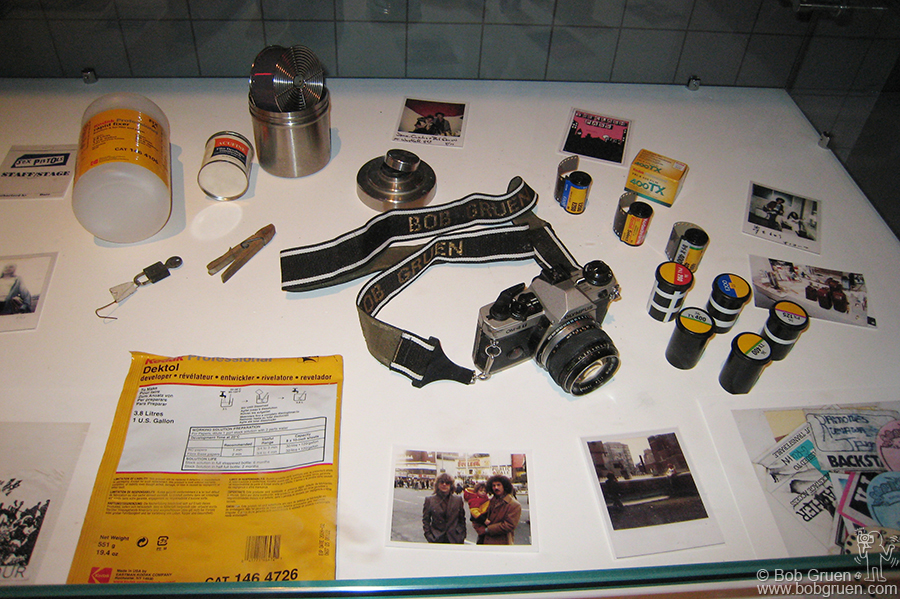 Artifacts on display include one of Bob's Olympus cameras, a film developing tank, rolls of film, original '70s copies of Rock Scene and Creem magazines along with Bob's books and other assorted items.
