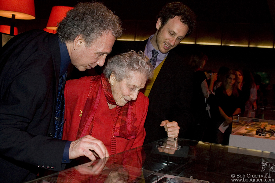 Bob shows his mom and son the display case with his cameras and copies of Rock Scene and Creem magazines.