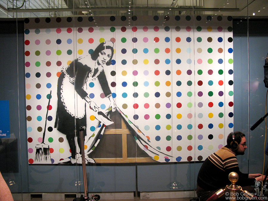 A painting by Banksy at the auction pokes fun at Damien's spot art paintings.
