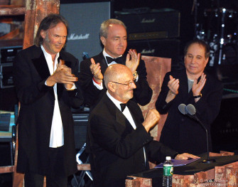 "Neil Young, Lorne Michaels, and Paul Simon inducted Warner Record's Mo Ostin who developed the careers of many of the Hall of Fame's members. Neil said he felt the country was like a ""gas guzzlin' SUV speeding down the road and the driver is drunk"". He apologised for talking politics, but added ""We're having a good time tonight, but we're going to kill a lot of people next week so let's not forget it""."
