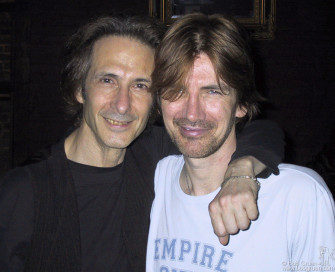 After the show, Lenny Kaye gives bass player Tony Shanahan a hug as Tony celebrates his birthday.