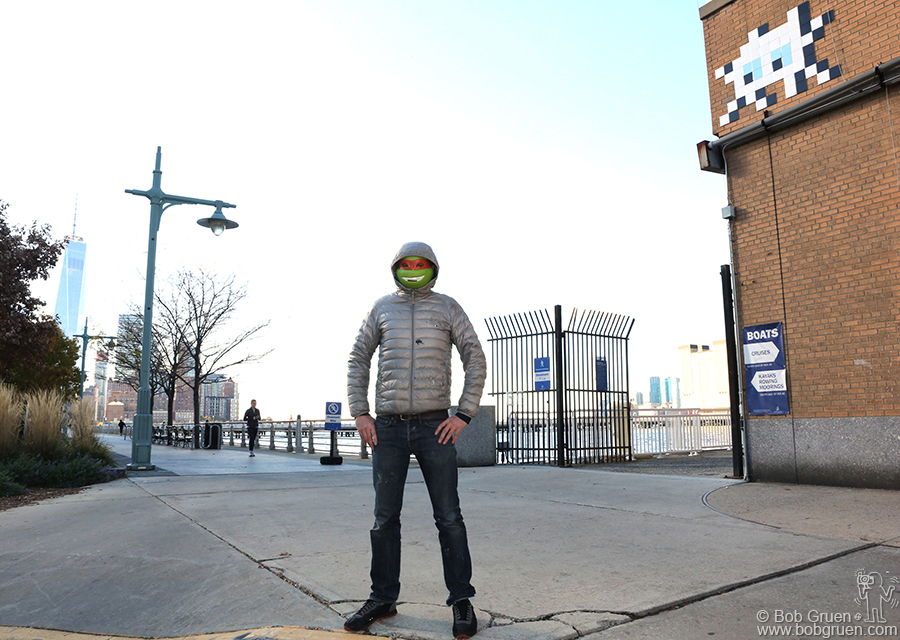 Nov 23 - NYC - World famous graffiti artist Invader posing in front of his work at Pier 40 on the Hudson River.