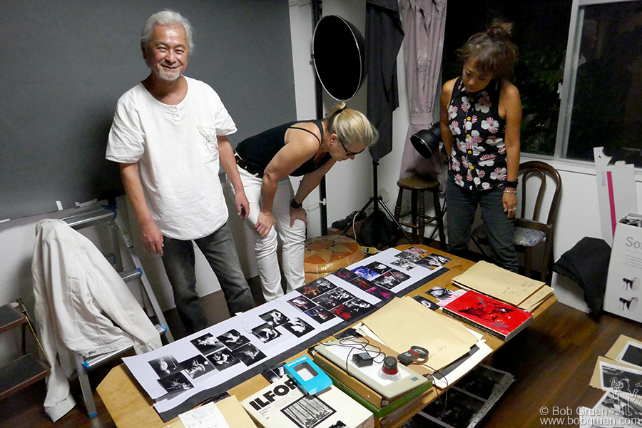 Aug 6 – Tokyo – My wife Elizabeth Gregory-Gruen and Yuki Taira check out the photos my friend, photographer Gin Satoh was showing us as he planned his exhibition of Iggy Pop photos.