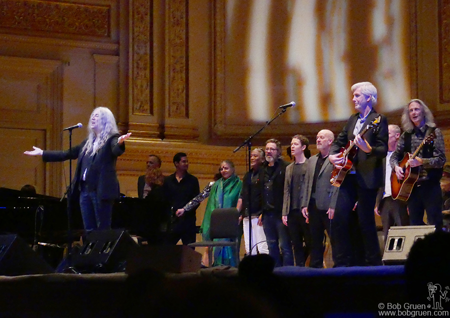 "Nov 5 – NYC – (L-R) Patti Smith, Jo Scheuer, Unknown, Dr. Vandana Shiva, Tenzin Choegyal, Olafur, Unknown, Michael Stipe of REM, Tony Shanahan of the Patti Smith Group, Flea of the Red Hot Chili Peppers and Lenny Kaye of the Patti Smith Group on stage during the ""Pathway To Paris"" concert at Carnegie Hall."
